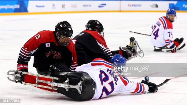 Zdenek Habl of Czech Republic battles for the puck with Eiji Misawa of Japan in the Ice Hockey Preliminary Round Group B game between Czech Republic...