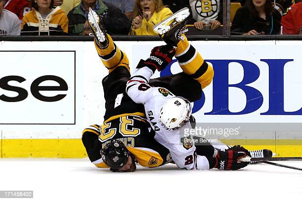 Zdeno Chara of the Boston Bruins and Brandon Saad of the Chicago Blackhawks fall to the after a check in Game Six of the 2013 NHL Stanley Cup Final...