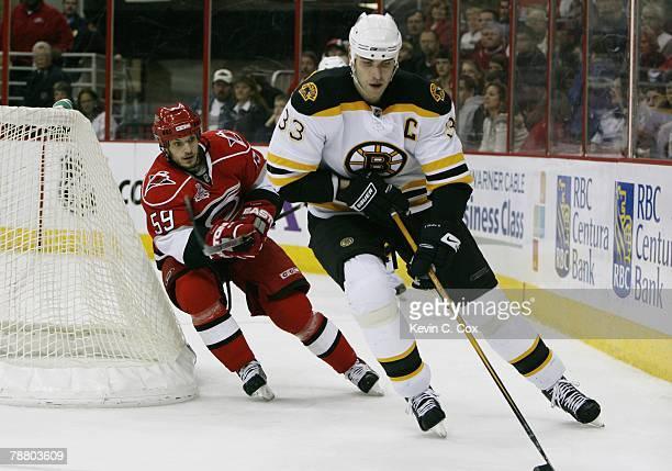 Zdeno Chara of the Boston Bruins and Chad LaRose of the Carolina Hurricanes skate during the NHL game at the RBC Center on December 28, 2007 in...