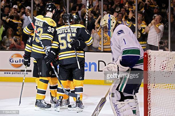 Zdeno Chara of the Boston Bruins and Johnny Boychuk celebrate as Roberto Luongo of the Vancouver Canucks looks down after a goal during Game Three of...