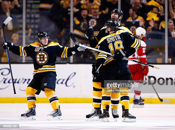 Zdeno Chara of the Boston Bruins celebrates his goal at the end of the second period with teammates Reilly Smith and Torey Krug against the Detroit...