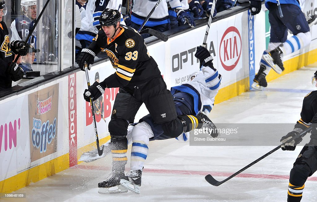 Zdeno Chara #33 of the Boston Bruins checks against a player of the Winnipeg Jets at the TD Garden on January 21, 2013 in Boston, Massachusetts.