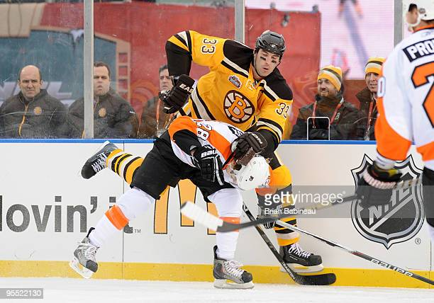 Zdeno Chara of the Boston Bruins checks against the Claude Giroux of Philadelphia Flyers in the 2010 Bridgestone Winter Classic at Fenway Park on...