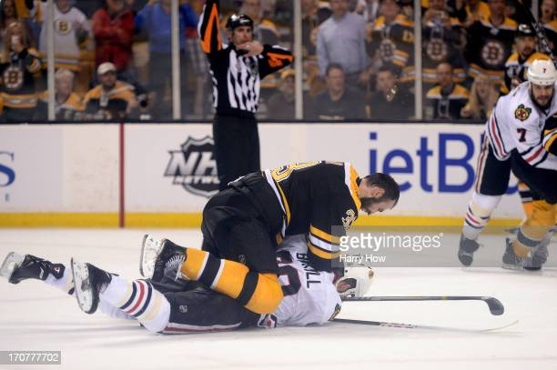 Zdeno Chara of the Boston Bruins checks Bryan Bickell of the Chicago Blackhawks to the ice late in the game in Game Three of the 2013 NHL Stanley Cup...