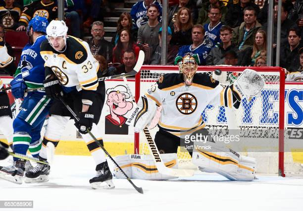 Zdeno Chara of the Boston Bruins checks Joseph Cramarossa of the Vancouver Canucks as Tuukka Rask of the Boston Bruins watches a shot during their...