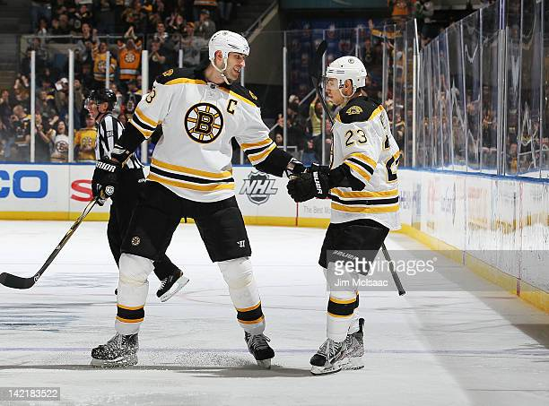 Zdeno Chara of the Boston Bruins congratulates teammate Chris Kelly on his second period goal against the New York Islanders on March 31 2012 at...