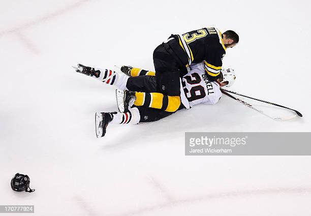 Zdeno Chara of the Boston Bruins fights Bryan Bickell of the Chicago Blackhawks in the third period during Game Three of the Stanley Cup Final on...