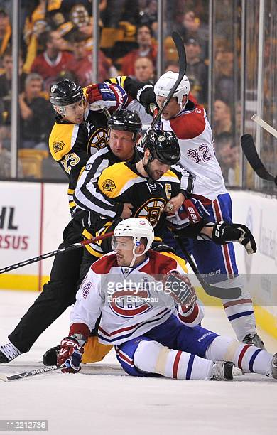 Zdeno Chara of the Boston Bruins gets held back by the referee during the game against the Montreal Canadiens in Game One of the Eastern Conference...