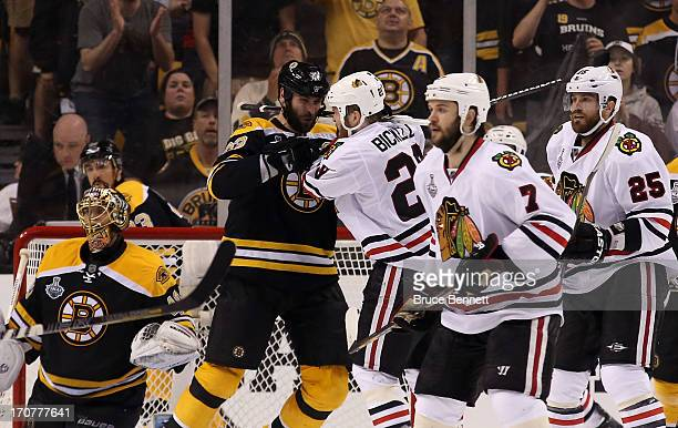 Zdeno Chara of the Boston Bruins gets tangled up with Bryan Bickell of the Chicago Blackhawks late in the game in Game Three of the 2013 NHL Stanley...