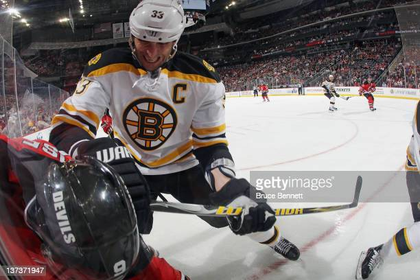 Zdeno Chara of the Boston Bruins hits Zach Parise of the New Jersey Devils along the boards at the Prudential Center on January 19, 2012 in Newark,...