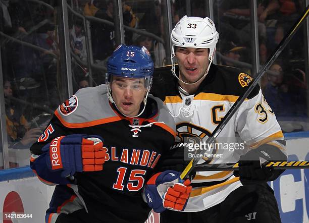 Zdeno Chara of the Boston Bruins rides PA Parenteau of the New York Islanders into the boards at the Nassau Veterans Memorial Coliseum on March 31...