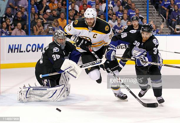 Zdeno Chara of the Boston Bruins tries to get the puck before Dwayne Roloson and Mike Lundin of the Tampa Bay Lightning during the second period in...