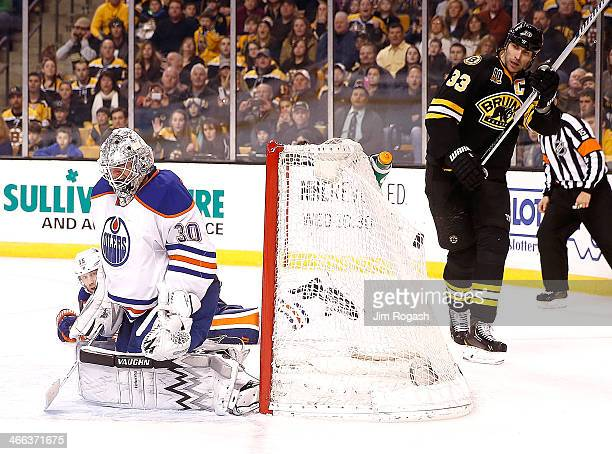 Zdeno Chara of the Boston Bruins watches as a shoot by teammate Torey Krug not seen passes by goalie Ben Scrivens of the Edmonton Oilers to hit back...