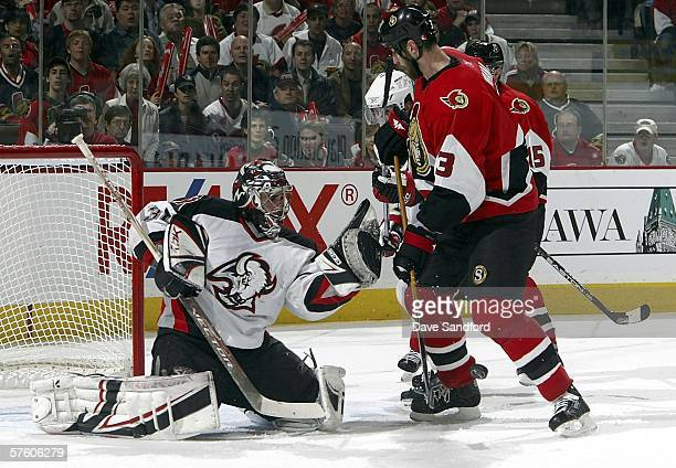 Zdeno Chara of the Ottawa Senators closes in on Ryan Miller of the Buffalo Sabres as he makes a glove save in game five of the Eastern Conference...