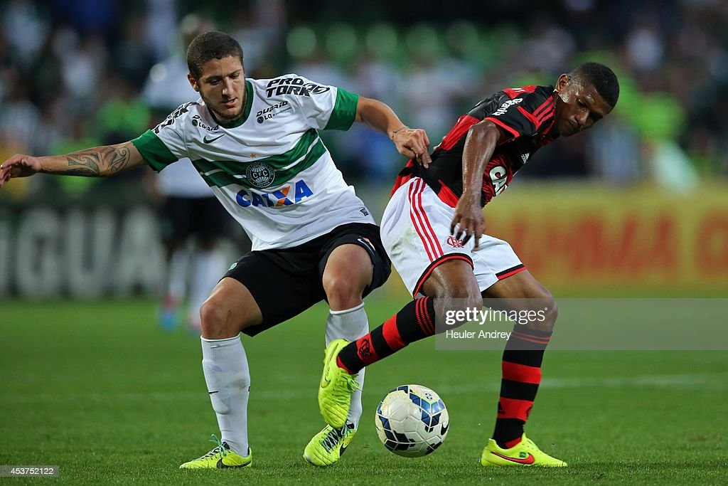 Ze Rafael of Coritiba competes for the ball with Marcio Araujo of Flamengo during the match between Coritiba and Flamengo for the Brazilian Series A 2014 at Couto Pereira stadium on August 17, 2014 in Curitiba, Brazil.