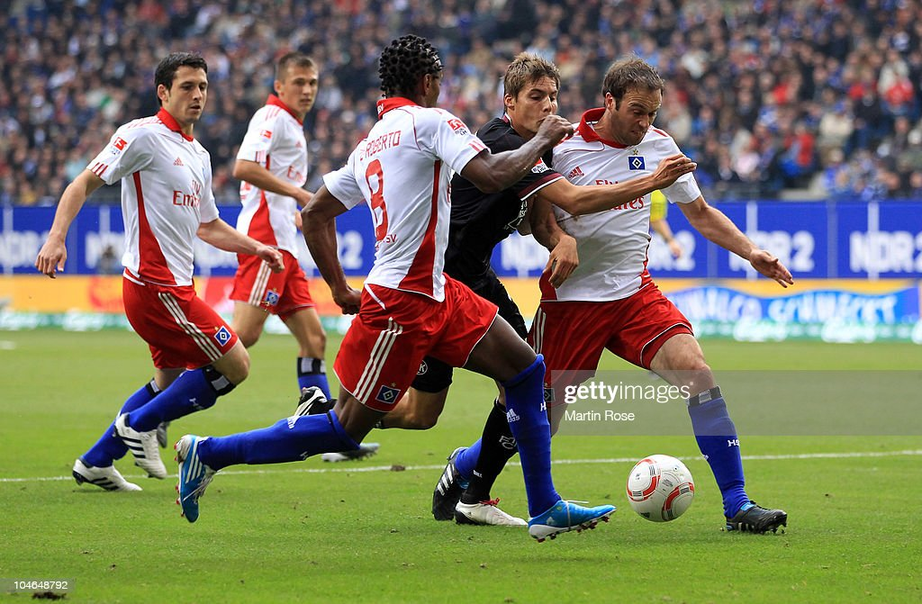 Ze Roberto (L),and Joris Mathijsen (R) of Hamburg and Clemens Walch (C) of Kaiserslautern compete for the ball during the Bundesliga match between Hamburger SV and 1. FC Kaiserslautern at Imtech Arena on October 2, 2010 in Hamburg, Germany.