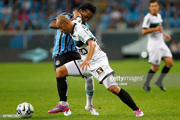 Ze Roberto of Gremio battles for the ball against Marcao of Figueirense during the match Gremio v Figueirense as part of Brasileirao Series A 2014 at...