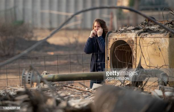 Zeatra Saylors looks on while her husband sifts through the ashes of their burned home in Paradise California on November 18 2018 His family lost a...
