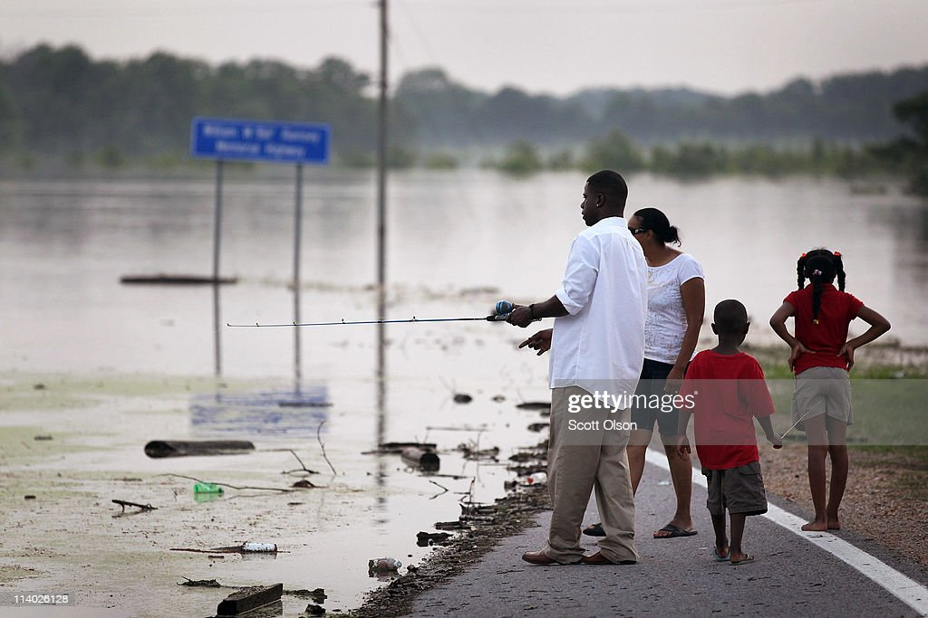 Zebedee Anderson (L) along with members of the family fish while standing on a section flooded of the Bill Ramsey Memorial Highway May 10, 2011 near Vicksburg, MS. The Mississippi river at Vicksburg is expected to rise an additional four feet by Thursday. Heavy rains have left the ground saturated, rivers swollen, and have caused widespread flooding in Mississippi, Missouri, Illinois, Kentucky, Tennessee, and Arkansas.
