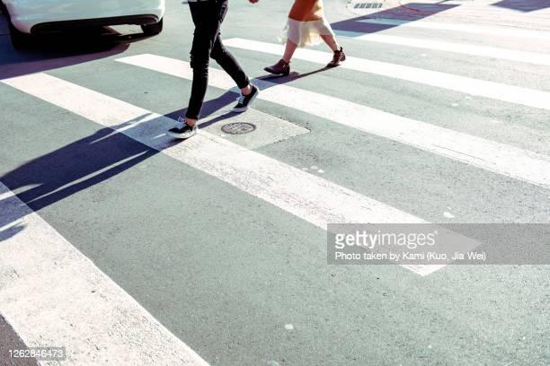 zebra crossing in the sun at taipei street,  two pedestrians walked on it make a long shadow, and a car is leaving. city scenes. - oversteken stockfoto's en -beelden