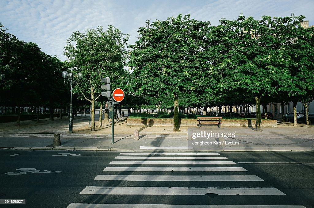 Zebra Crossing On City Street With Road Sign On Sidewalk Against Sky : Stock-Foto