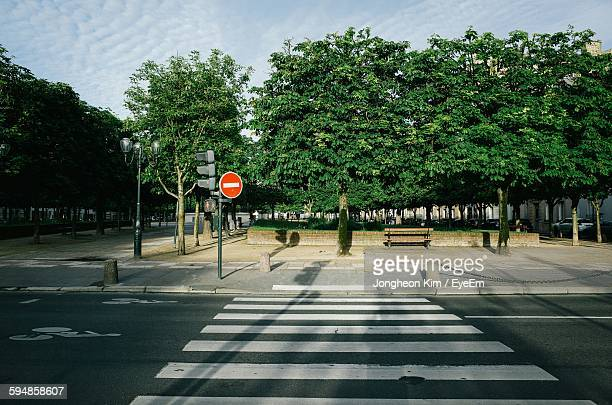 zebra crossing on city street with road sign on sidewalk against sky - pedestrian crossing imagens e fotografias de stock