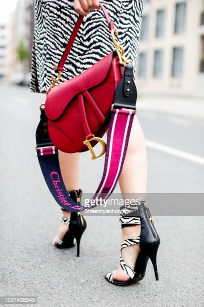 Zebra heels by Balmain and a bordeaux colored saddle bag by Dior as a detail of influencer Dany Michalski during a street style shooting on July 15...
