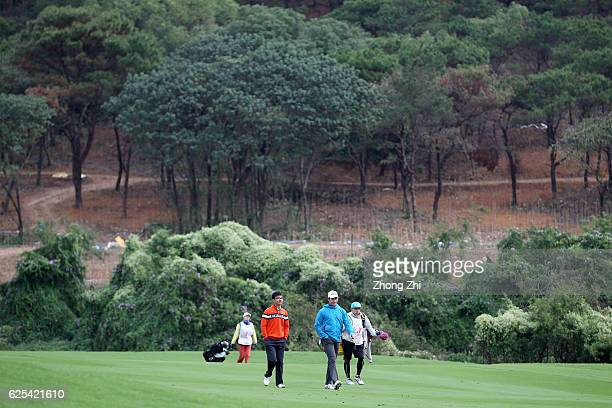 Zecheng Dou of China and Charlie Saxon walk during the first round of the Buick open at Guangzhou Foison Golf Club on November 24 2016 in Guangzhou...