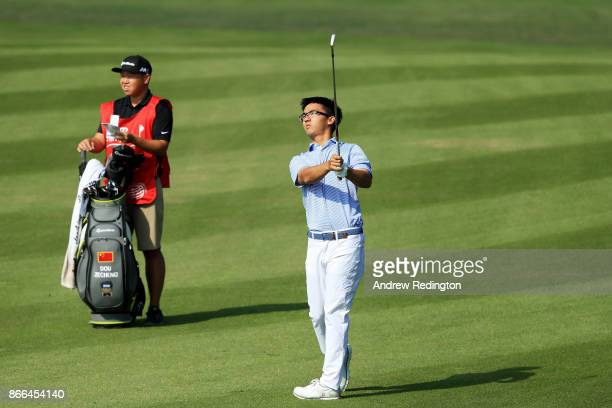 Zecheng Dou of China plays a shot on the 13th hole as his caddie looks on during the first round of the WGC HSBC Champions at Sheshan International...