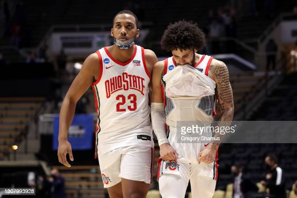 Zed Key and Duane Washington Jr. #4 of the Ohio State Buckeyes react after losing to the Oral Roberts Golden Eagles in overtime in the first round...