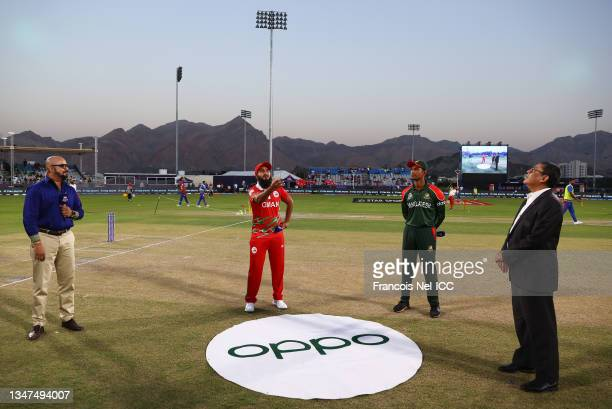 Zeeshan Maqsood of Oman flips the coin as Mahmudullah of Bangladesh looks on ahead of the ICC Men's T20 World Cup match between Bangladesh and Oman...
