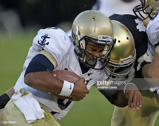 Zeke Motta of the Notre Dame Fighting Irish crashes head-to-head with Trey Miller of the Navy Midshipmen at Notre Dame Stadium on October 29, 2011 in...