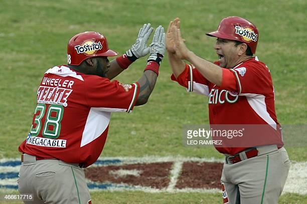 Zelous Wheeler of Mexico's Naranjeros de Hermosillo celebrates with a teammate during their 2014 Caribbean baseball series game against Puerto Rico's...