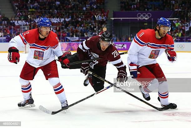 Zemgus Girgensons of Latvia falls to the ice against Marek Zidlicky and Martin Hanzal of Czech Republic in the third period during the Men's Ice...
