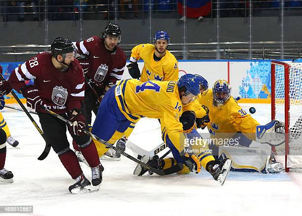 Zemgus Girgensons of Latvia shoots and scores against Henrik Lundqvist of Sweden in the third period during the Men's Ice Hockey Preliminary Round...