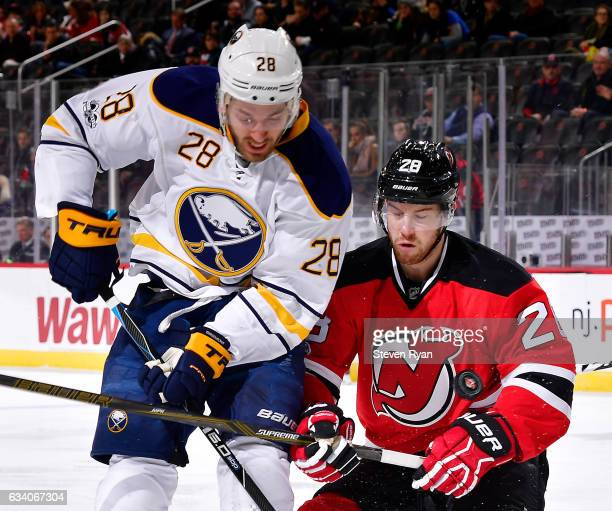 Zemgus Girgensons of the Buffalo Sabres and Damon Severson of the New Jersey Devils battle for the puck during the first period at Prudential Center...