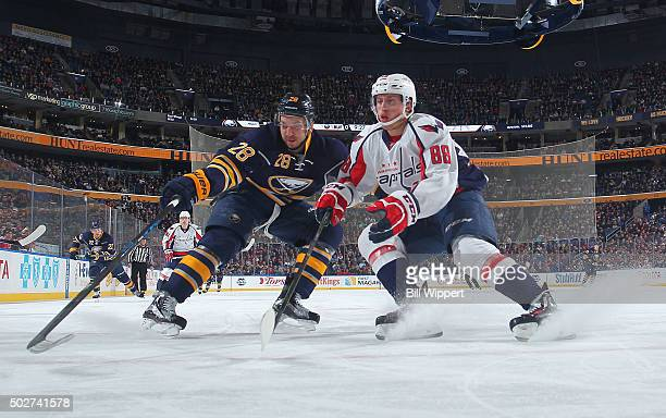 Zemgus Girgensons of the Buffalo Sabres and Nate Schmidt of the Washington Capitals battle for the puck during an NHL game on December 28 2015 at the...