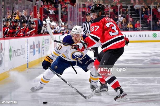 Zemgus Girgensons of the Buffalo Sabres and Pavel Zacha of the New Jersey Devils battle for the puck during the first period at Prudential Center on...