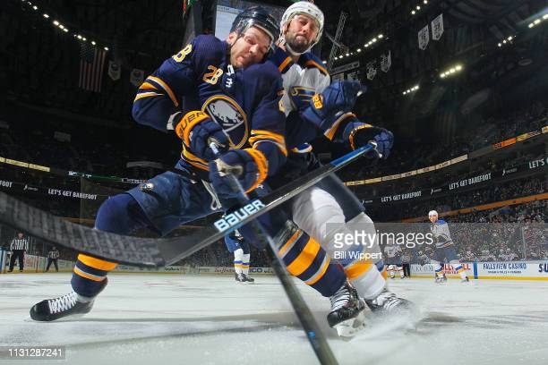 Zemgus Girgensons of the Buffalo Sabres and Robert Bortuzzo of the St Louis Blues battle along the boards during an NHL game on March 17 2019 at...