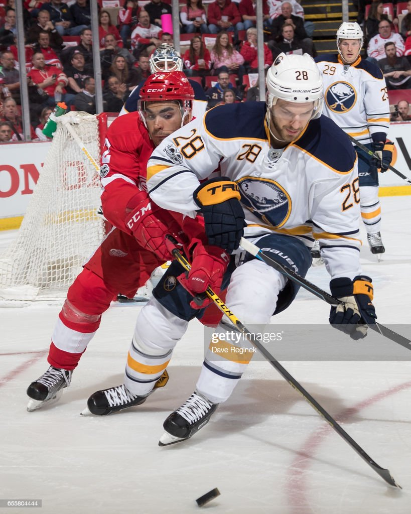Zemgus Girgensons #28 of the Buffalo Sabres battles for the puck with Andreas Athanasiou #72 of the Detroit Red Wings during an NHL game at Joe Louis Arena on March 20, 2017 in Detroit, Michigan.