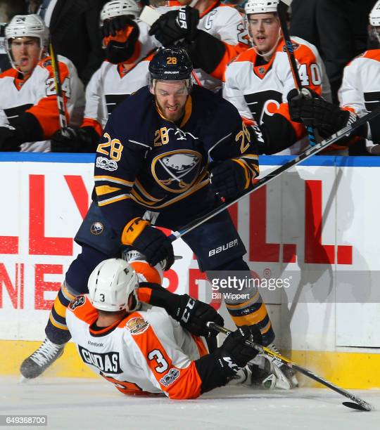 Zemgus Girgensons of the Buffalo Sabres checks Radko Gudas of the Philadelphia Flyers during an NHL game at the KeyBank Center on March 7 2017 in...