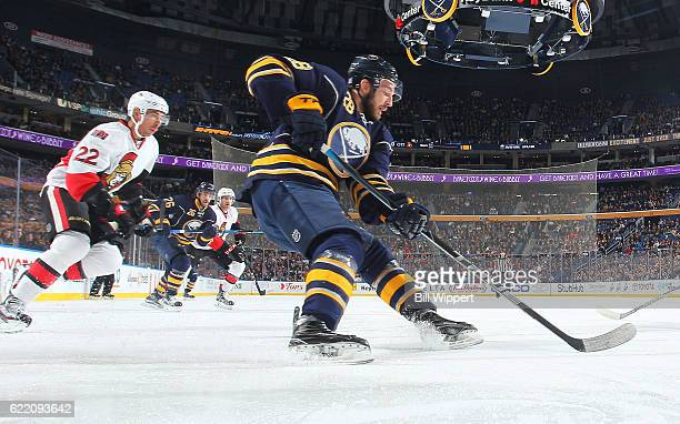Zemgus Girgensons of the Buffalo Sabres controls the puck against Chris Kelly of the Ottawa Senators during an NHL game at the KeyBank Center on...