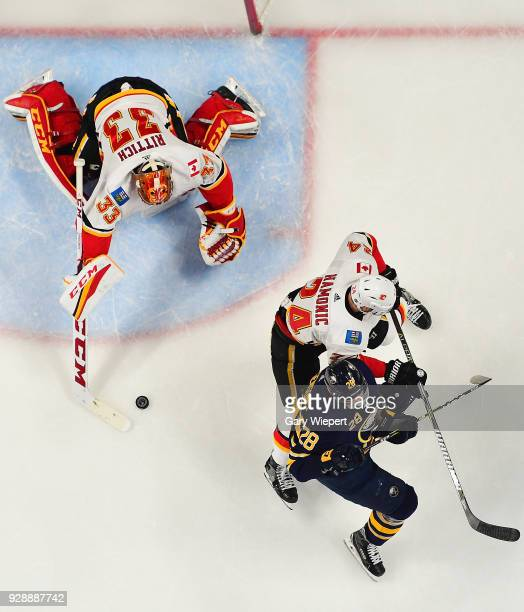 Zemgus Girgensons of the Buffalo Sabres is defended by David Rittich and Travis Hamonic of the Calgary Flames during an NHL game on March 7 2018 at...