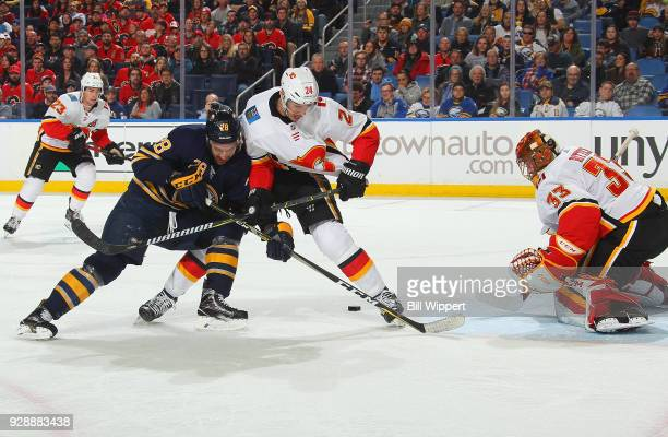 Zemgus Girgensons of the Buffalo Sabres is defended by Travis Hamonic and David Rittich of the Calgary Flames during an NHL game on March 7 2018 at...