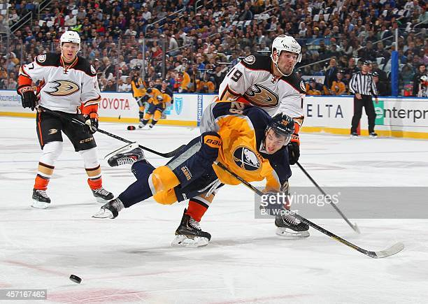Zemgus Girgensons of the Buffalo Sabres is upended by Patrick Maroon of the Anaheim Ducks on October 13 2014 at the First Niagara Center in Buffalo...