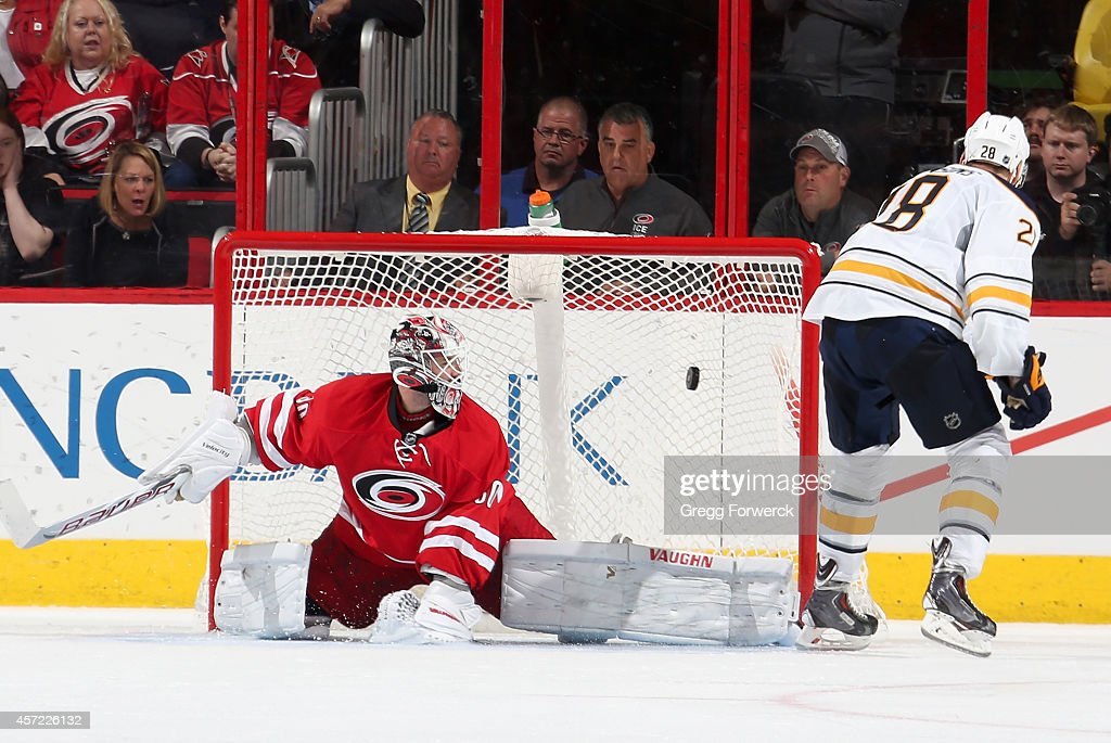 Zemgus Girgensons #28 of the Buffalo Sabres scores the winning goal of the shootout on Cam Ward #30 during their NHL game at PNC Arena on October 14, 2014 in Raleigh, North Carolina.