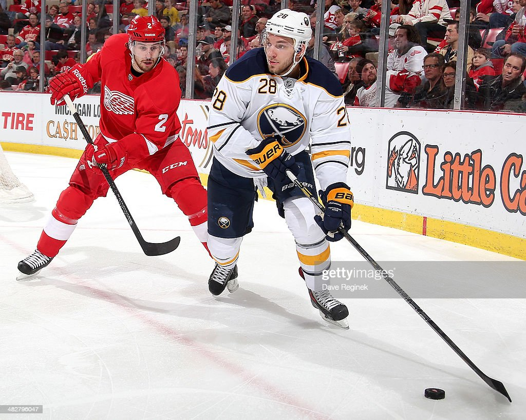 Zemgus Girgensons #28 of the Buffalo Sabres skates with the puck as Brendan Smith #2 of the Detroit Red Wings pressures him during an NHL game on April 4, 2014 at Joe Louis Arena in Detroit, Michigan.