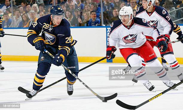 Zemgus Girgensons of the Buffalo Sabres skates with the puck in front of Ryan Craig of the Columbus Blue Jackets during their preseason game at First...