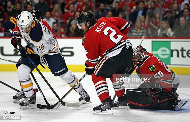 Zemgus Girgensons of the Buffalo Sabres tries to get off a shot against Duncan Keith and Corey Crawford of the Chicago Blackhawks at the United...
