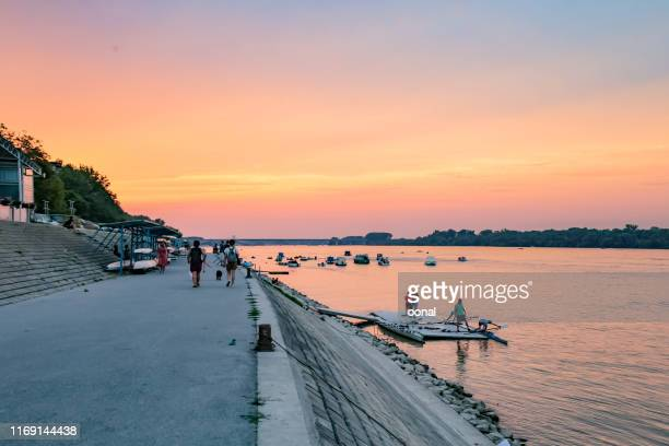 zemun quay coastline sunset landscape view with people and boats - quayside stock pictures, royalty-free photos & images